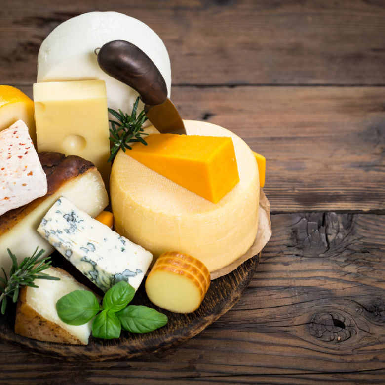 Various types of cheese on the wooden table